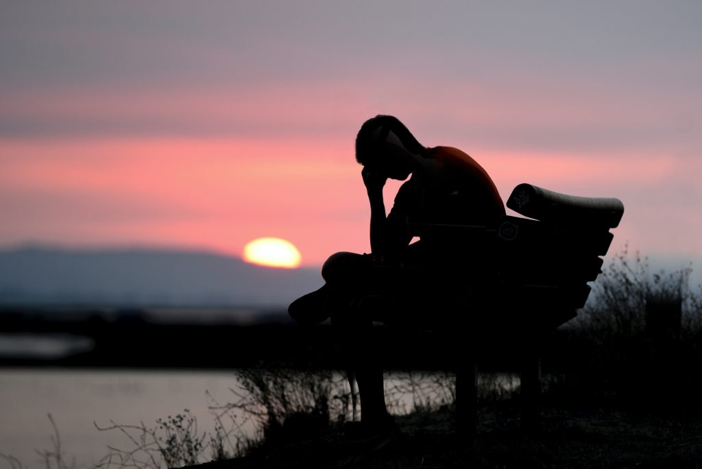 Silhouette of young man on park bench holding his head