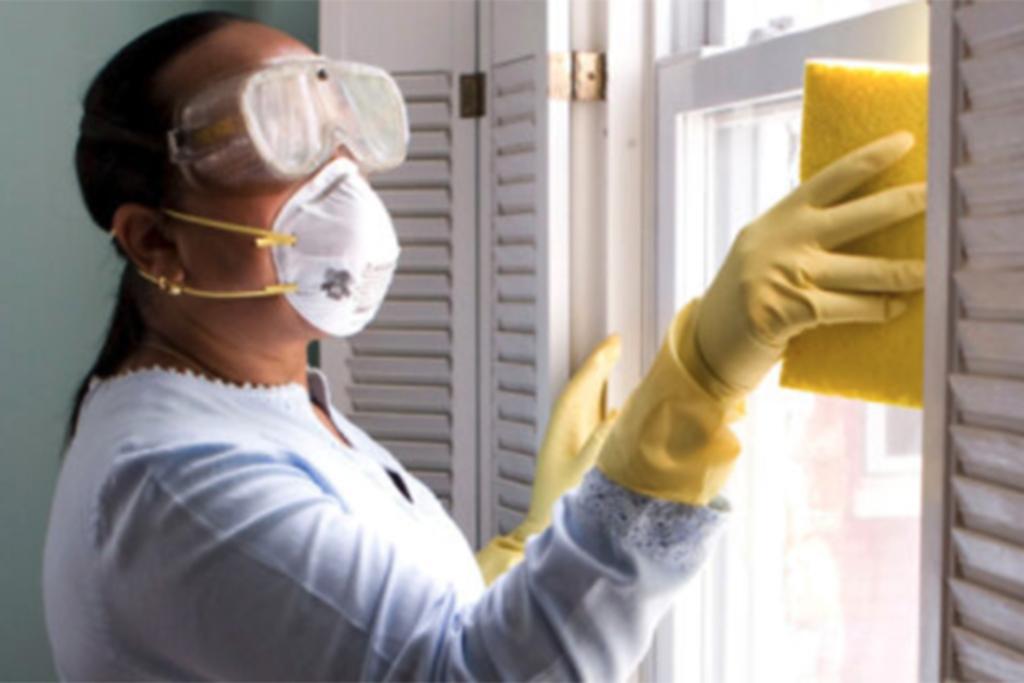 Woman wearing mask cleaning window