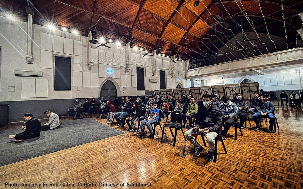 Afghani community praying in Church hall